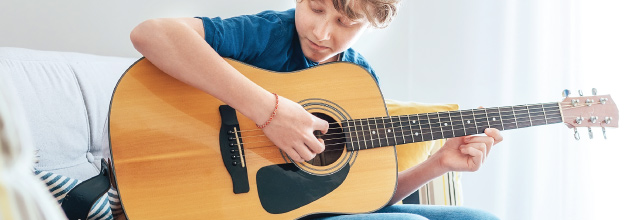 Teenage boy learning to play acoustic guitar