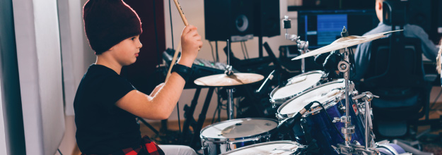 young boy playing drums in a recording studio