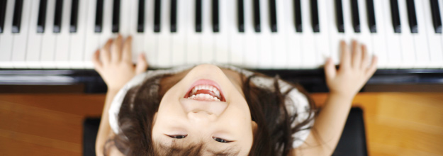young asian girl at piano looking up and smiling