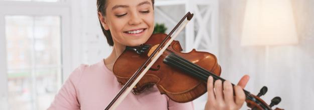 teenage girl playing violin and smiling