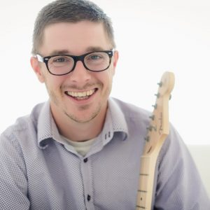 Cory Moon smiling and holding electric guitar