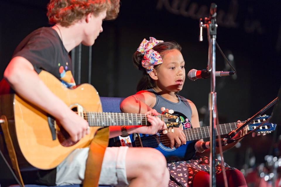young girl singing and playing guitar with instructor on stage