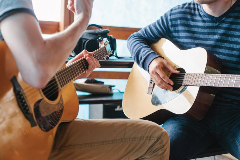 closeup of teenager receiving guitar lesson from qualified instructor, both holding acoustic guitars