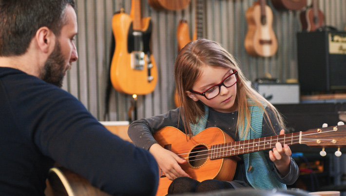 young girl receiving qualified instruction on how to play the ukulele