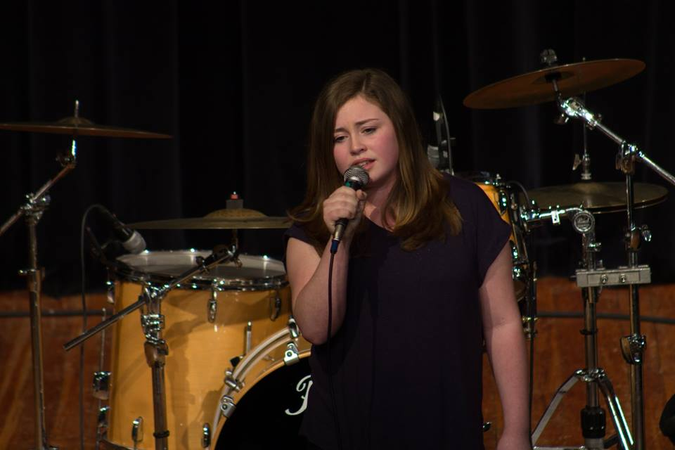 Young singer holding microphone on stage delivering a great performance